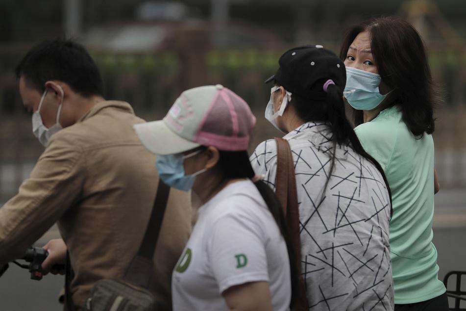 Menschen mit Mundschutz warten in Peking darauf, eine Straße zu überqueren. Neue Fälle von Coronaviren nehmen in der nordwestlichen Region Xinjiang in China extrem schnell zu.