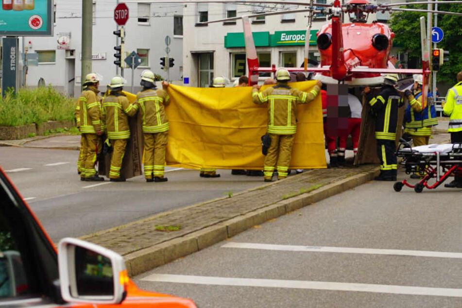 Feuerwehrleute halten eine Decke hoch, um die Sicht auf Verletzte zu verdecken.