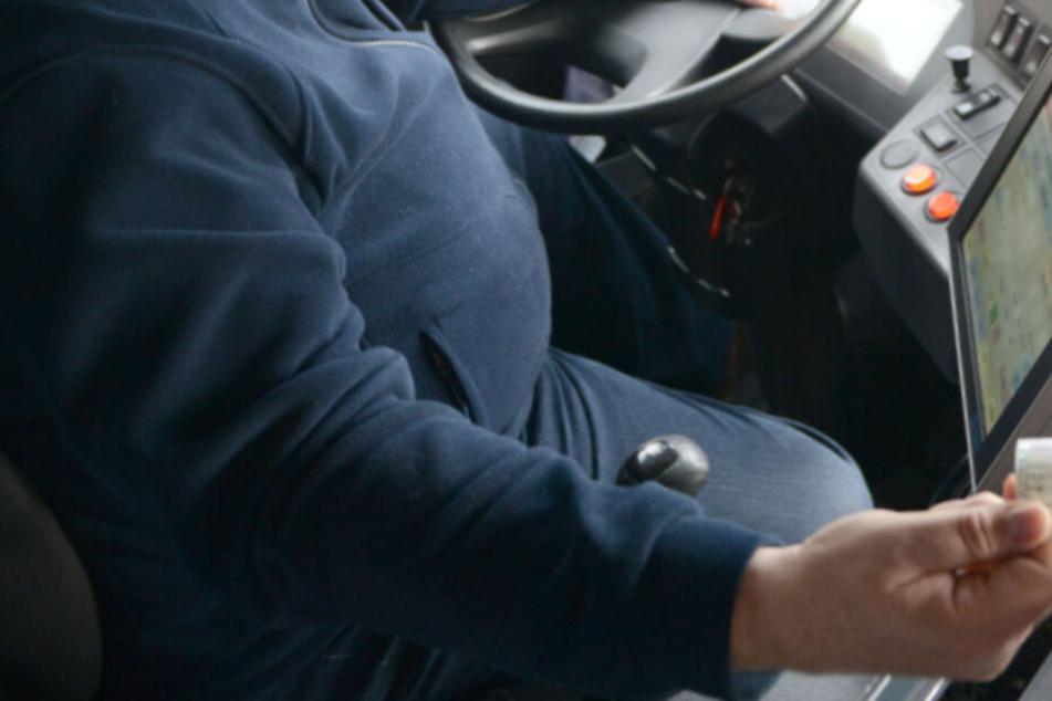 Ein Busfahrer überreicht einem Fahrgast sein Ticket (Symbolbild).