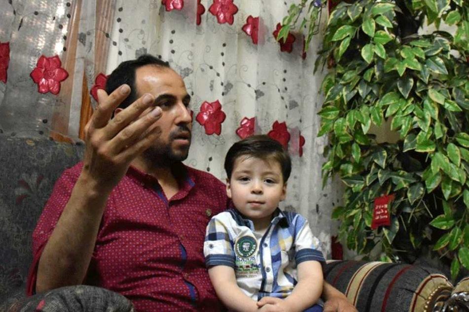 Der kleine Omran sitzt auf dem Schoß von Vater Mohammed Daknisch.
