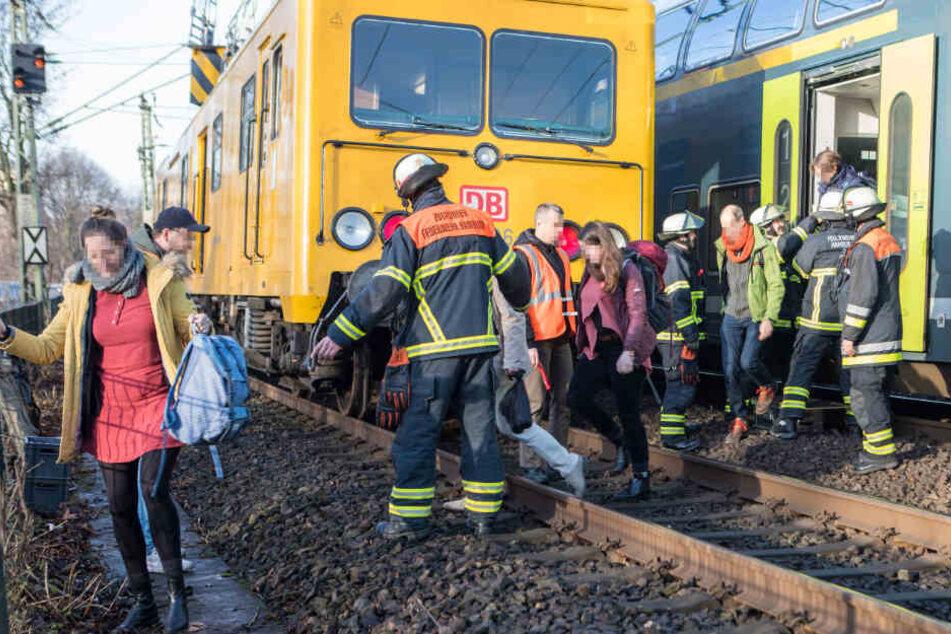 Feuerwehrleute evakuieren einen Zug nach einer Panne auf der Lombardsbrücke in Hamburg.