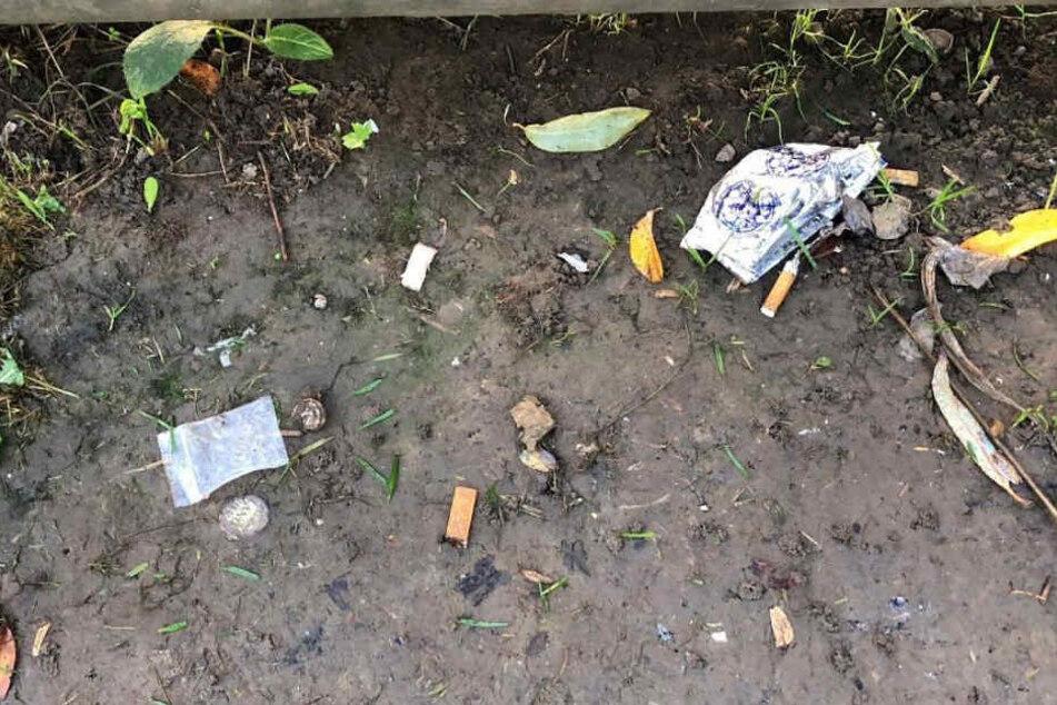 Überall liegt achtlos weggeworfener Müll herum, der auf Drogenkonsum hinweist.