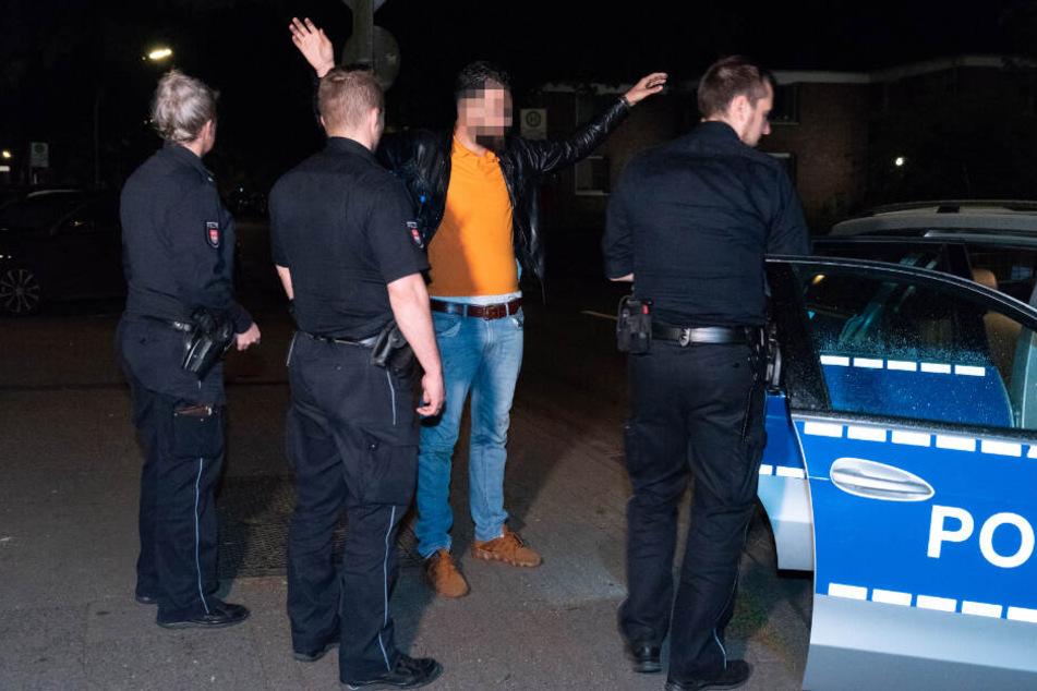 Ein Mann steht mit erhobenen Armen von Polizisten umringt am Tatort.