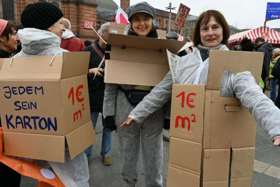 """Teilnehmerin der Demonstration """"Die Stadt muss allen gehören"""" in Bremen, haben sich für mehr bezahlbaren Wohnraum Kartons mit Sprüchen übergezogen."""