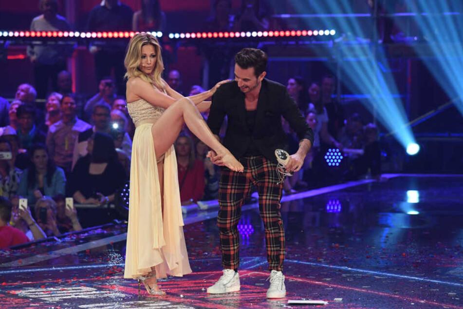 Florian zieht seiner Freundin Helene die Schuhe aus.