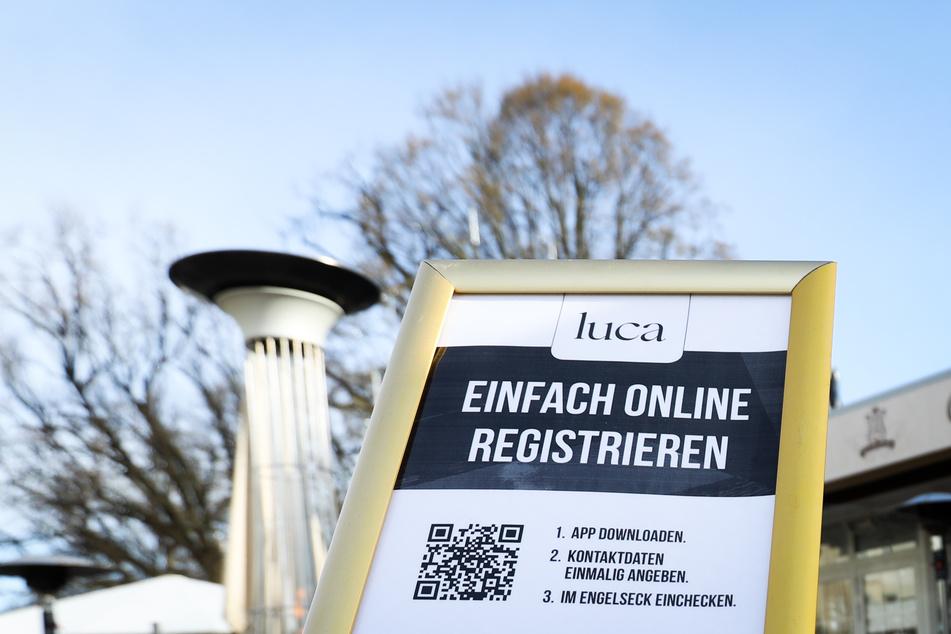 Ein Hinweisschild zur Nutzung der Luca-App ist am Eingang zu einem Cafe zu sehen. So können sich Gäste registrieren.