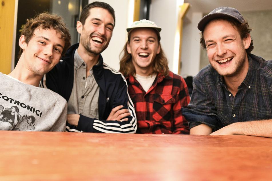 Die Mitglieder der Band AnnenMayKantereit, Henning May (v.l.n.r.), Christopher Annen, Malte Huck, und Severin Kantereit lächeln nach einem dpa-Interview in einem Konferenzraum. (Archivbild)