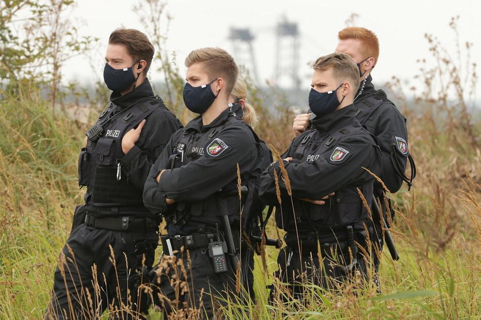 Polizei Beamten stehen im Tagebau Garzweiler an der Abbruchkante.