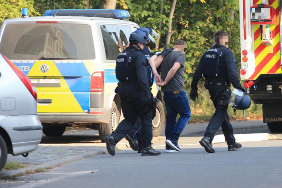 Die Polizei führt den Mann in Handschellen ab.