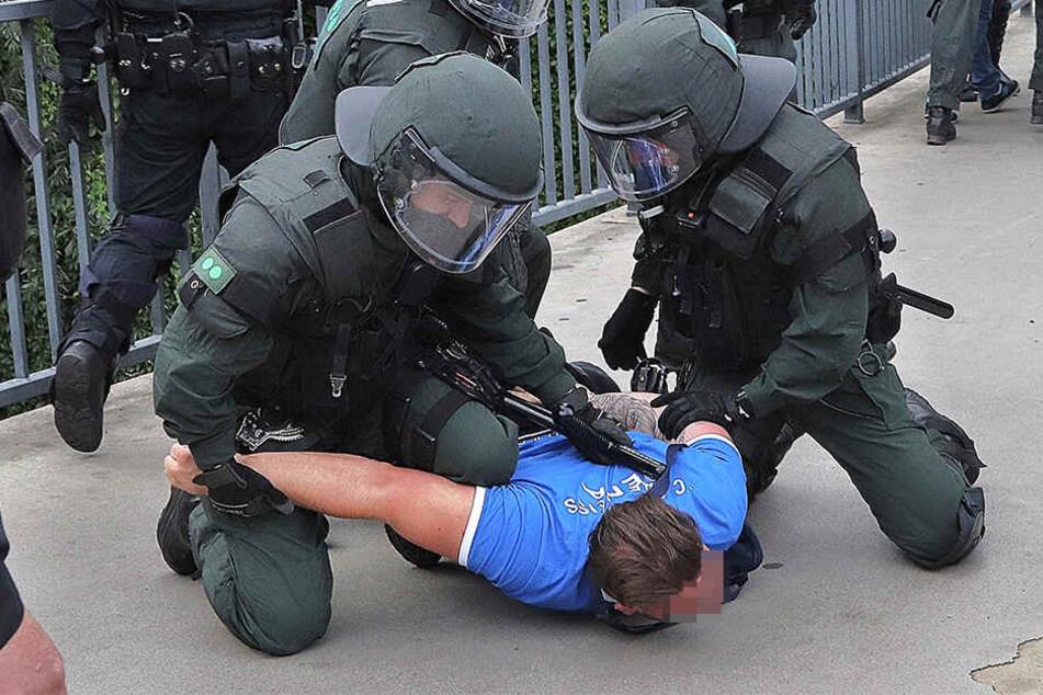 Ein Mann mit Carl Zeiss Jena T-Shirt wird von Bereitschaftspolizisten festgenommen.