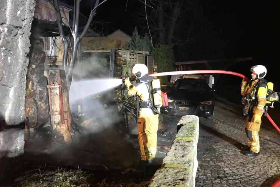 Feuerwehrleute löschen die Flammen am Schuppen.