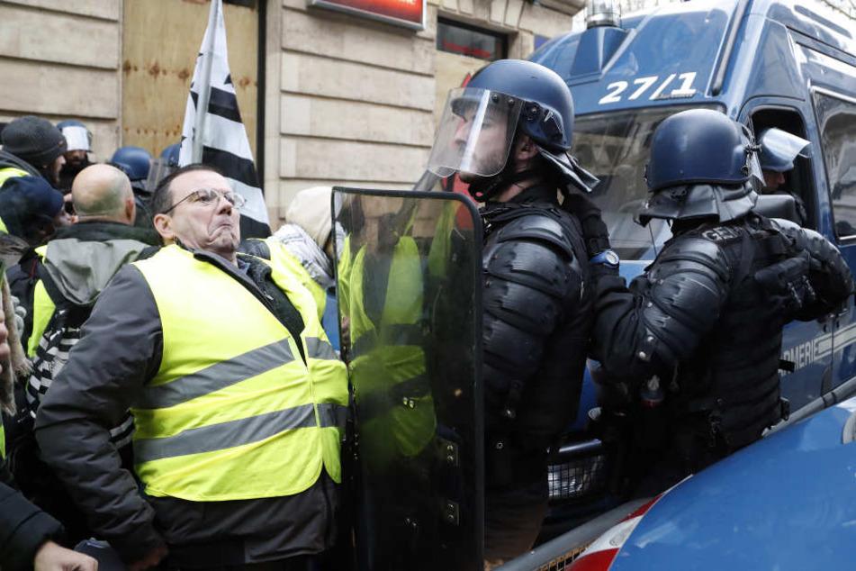 Demonstranten mit gelben Westen werden von Polizisten beim Betreten eine Straße in Paris aufgehalten.