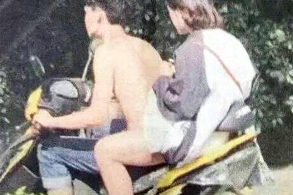 Die beiden sitzen auf dem Motorroller, der Fahrer scheinbar nackt.