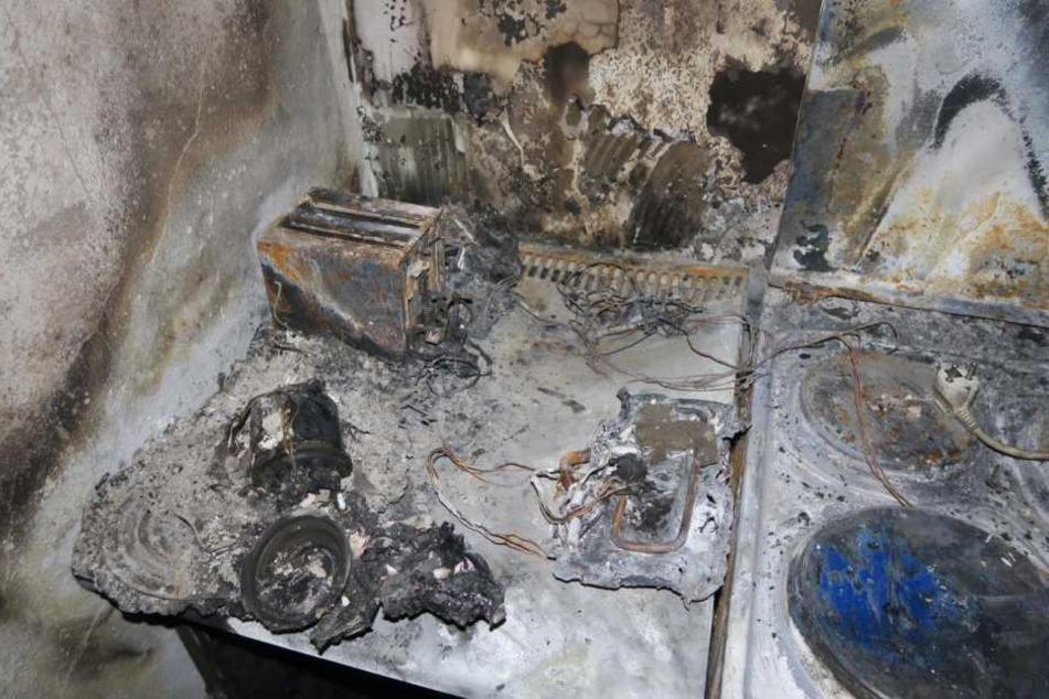 Auf einer Herdplatte liegt der Stecker einer Verteilersteckdose (r.). Sie soll Auslöser des verheerenden Brandes gewesen sein.