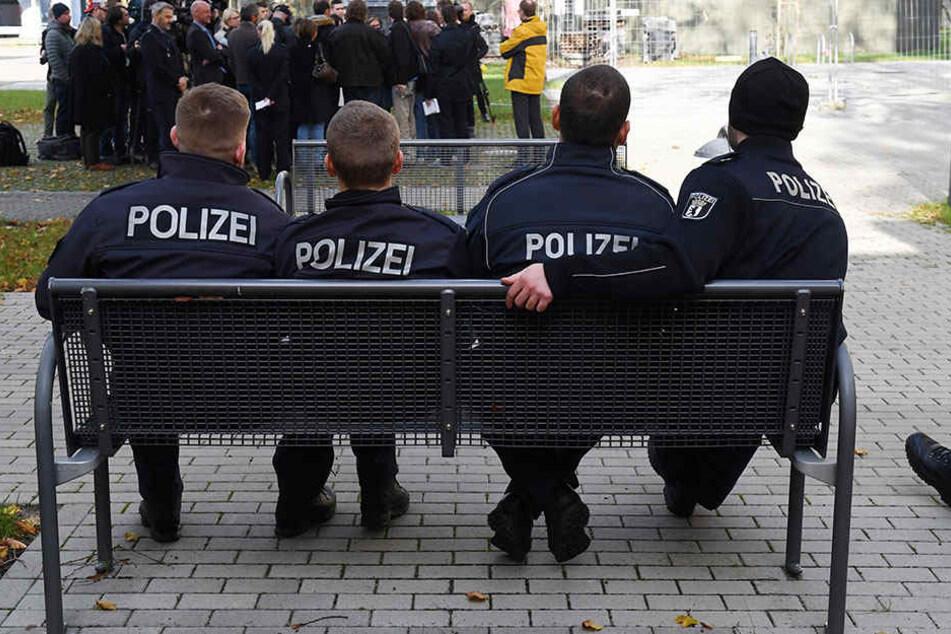 Berliner Polizeischüler auf einer Bank vor einem Ausbildungsgebäude.