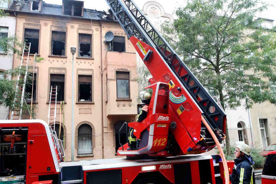 Feuerwehrleute untersuchen mit Hilfe einer Drehleiter das abgebrannte Haus.