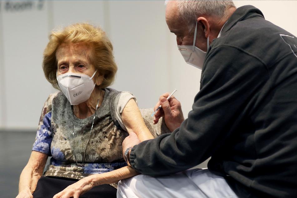 Ein Arzt hält im Impfzentrum die Spritze an den Arm von Elisabeth Steubesand (105). Die älteste Kölnerin hat kein Verständnis für Menschen, die ihre Impftermine absagen, weil ihnen der Impfstoff nicht passt.