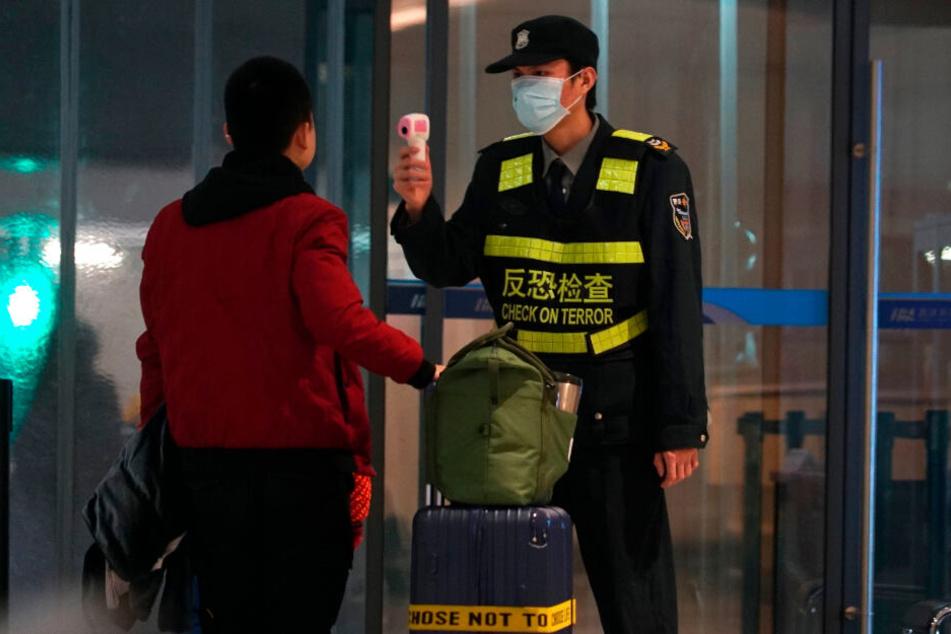 Ein Mitarbeiter des Flughafen Wuhan Tianhe International Airport trägt Mundschutz und misst bei einem Reisenden Temperatur.