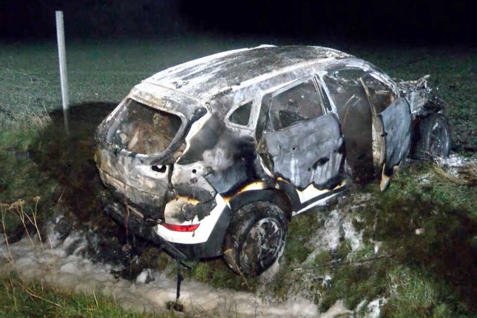 Der SUV steht ausgebrannt auf einer Wiese neben der A1.