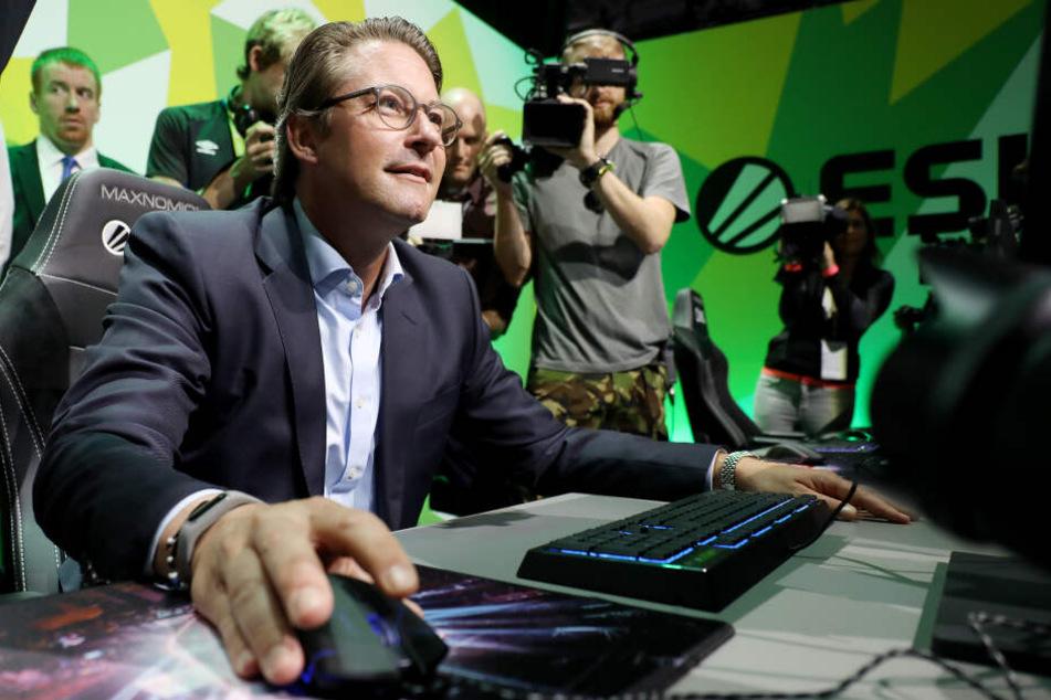 Andreas Scheuer (CSU), Bundesverkehrsminister, sitzt auf der Gamescom an einem Computerspiel.