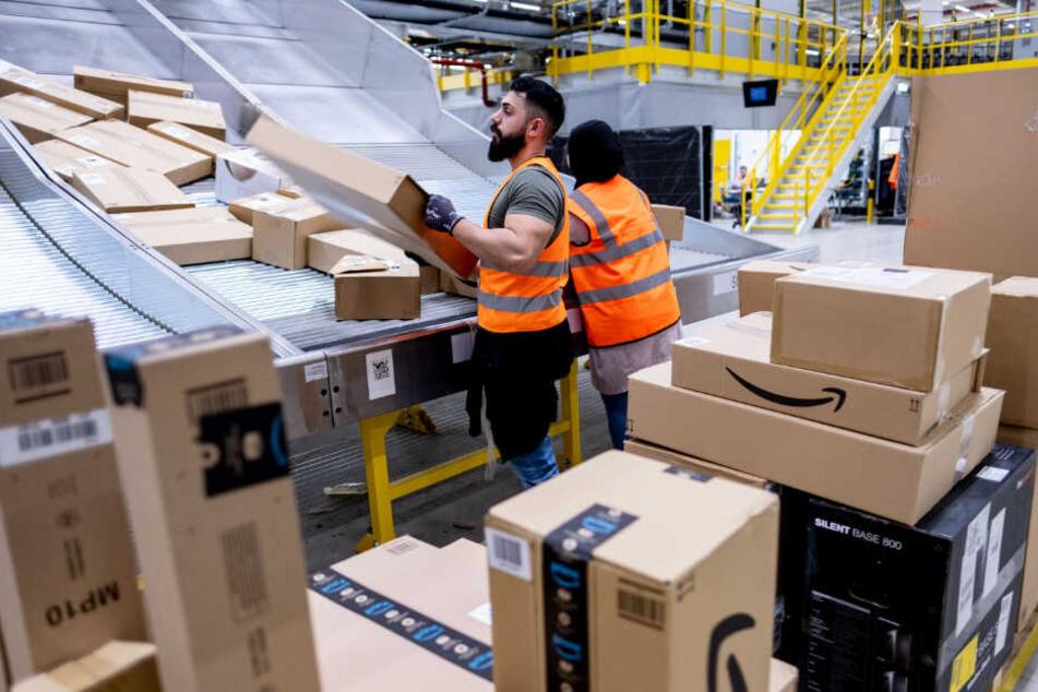 Amazon-Mitarbeiter sortieren Pakete im Versandzentrum. (Archivbild)