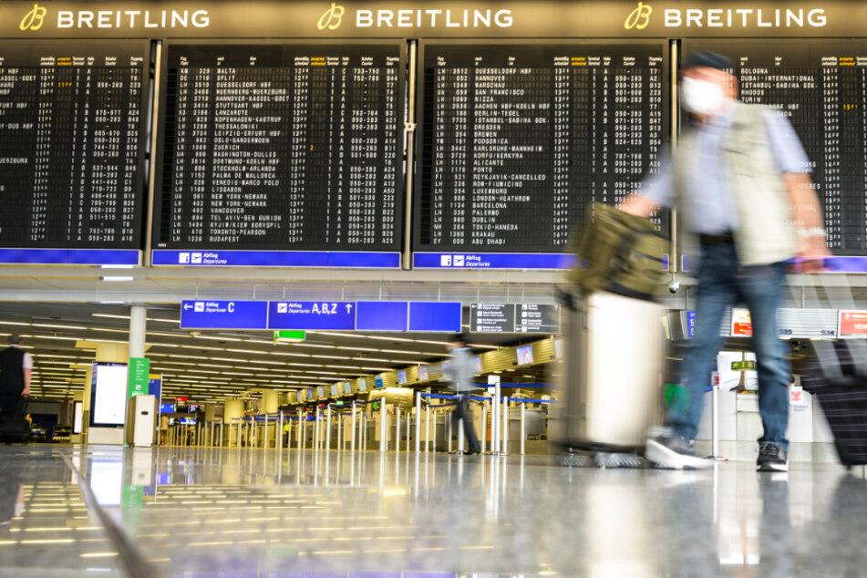 Reisende gehen im Juli mit Gepäck durch die Abflughalle im Terminal 1 am Flughafen Frankfurt.