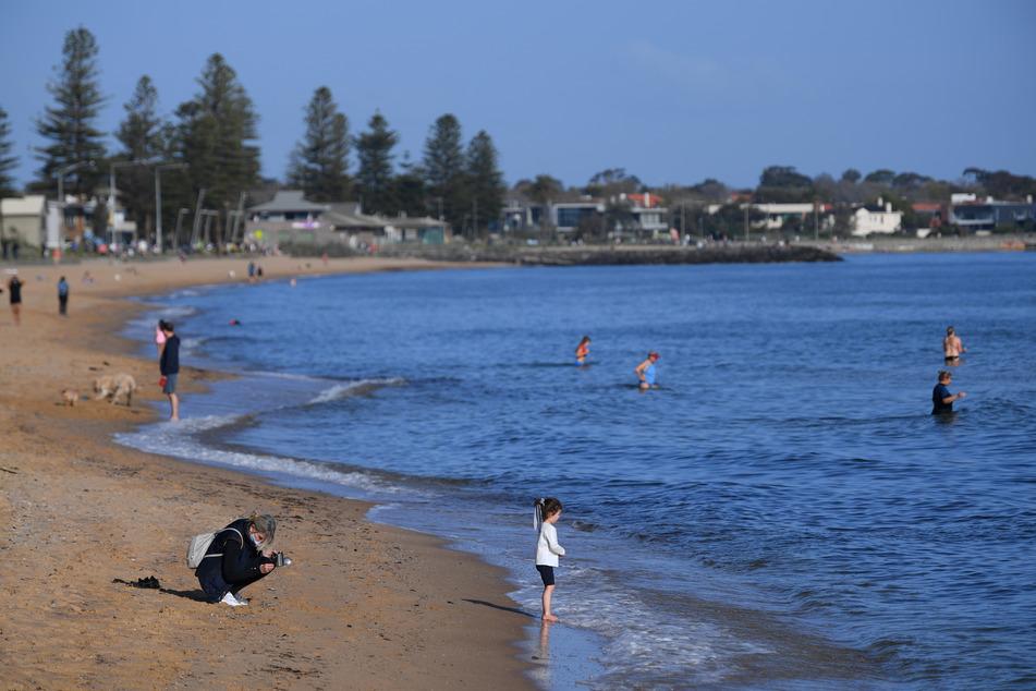 Am Elwood-Strand stehen und gehen Menschen, die die Sonne und das Meer genießen.