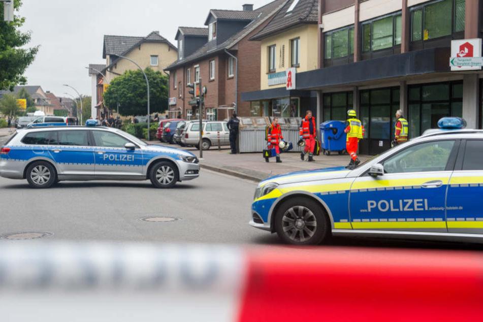 Polizei- und Rettungskräfte stehen vor dem Mehrfamilienhaus in Bargteheide, in dem die Frau erschossen wurde.