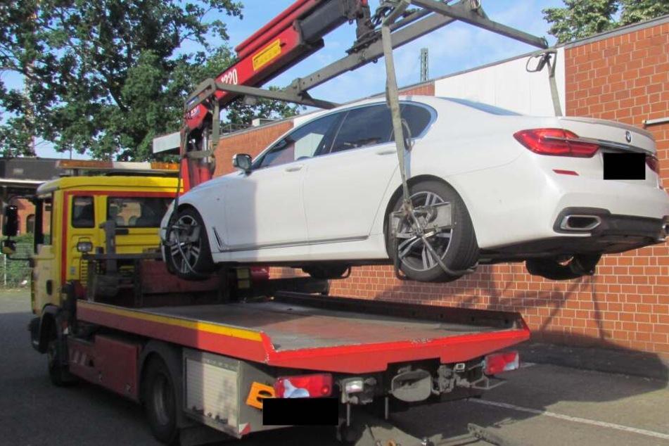 Ein gepfändeter, hochwertiger BMW wird nach der Razzia abgeschleppt.