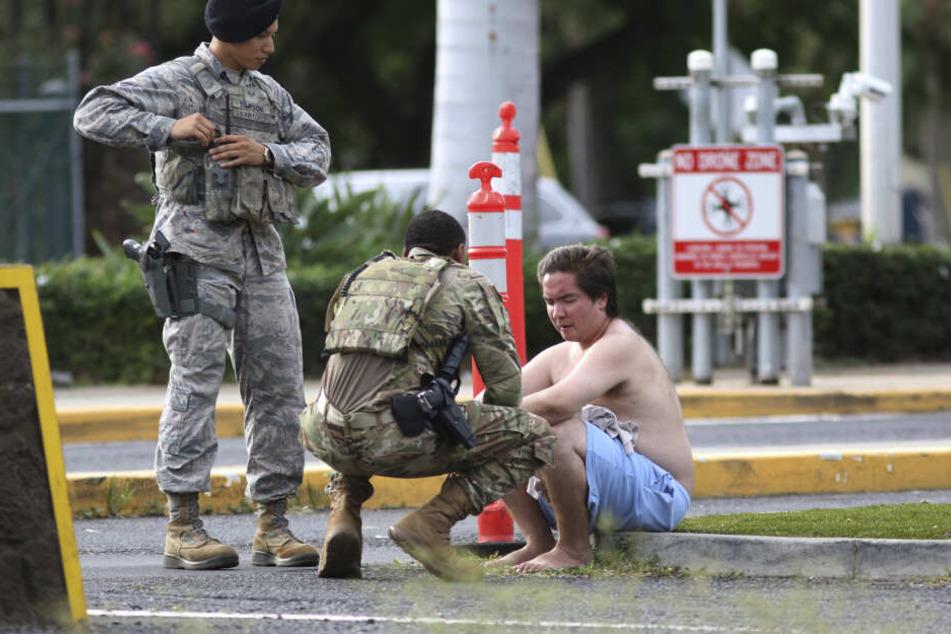 Sicherheitskräfte kümmern sich um einen nicht identifizierten Mann vor dem Haupttor des US-Militärstützpunkts Pearl Harbor-Hickam auf Hawaii