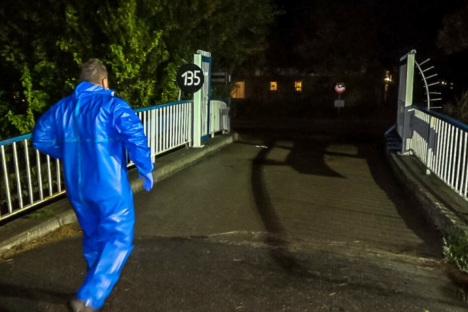 Ein Mann im blauen Ganzkörperschutzanzug geht in Richtung Campingplatz.