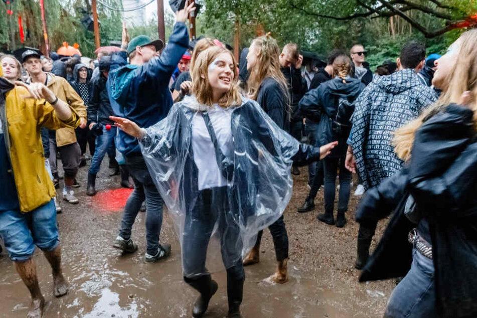 Besucher des Dockville-Festivals tanzen in Hamburg im Regen zur  House-Musik eines DJs.