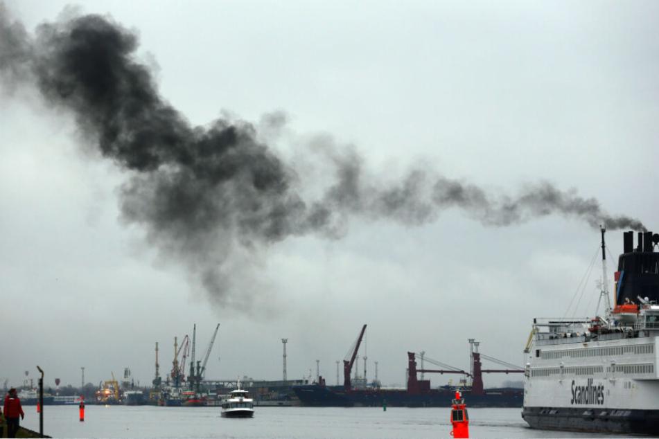 Eine dunkle Abgaswolke tritt aus dem Schornstein einer Ostsee-Fähre in Rostock aus. (Archivbild)