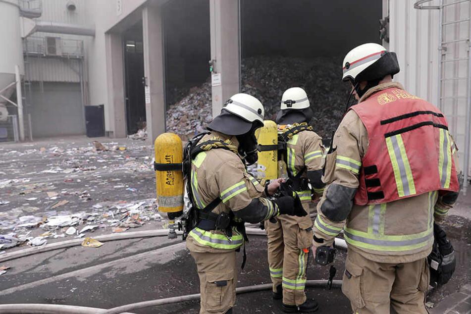 Die Feuerwehrmänner rücken mit Schutzkleidung und Atemgeräten in die Lagerhalle vor.