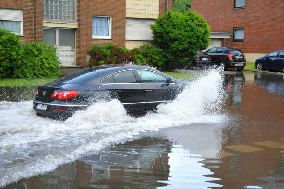 Ein Auto fährt durch eine überflutete Straße in Mönchengladbach.