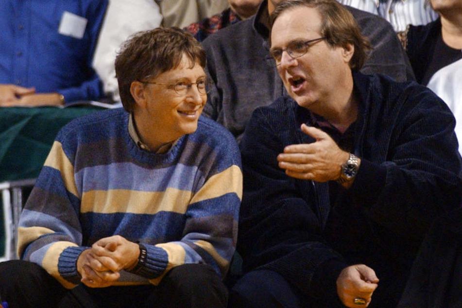 Bill Gates (l) und Paul Allen, beide Gründer von Microsoft, sitzen während eines Basketball-Spiels im Jahr 2003 nebeneinander.