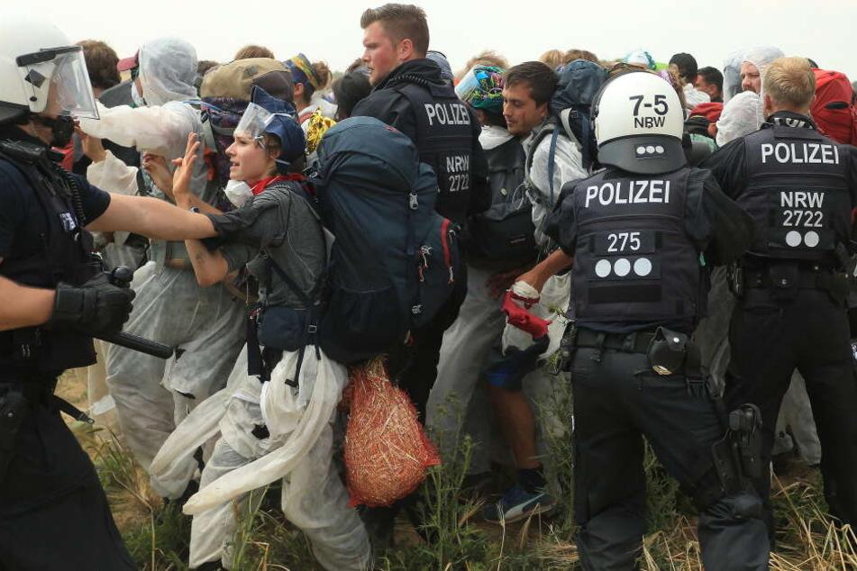 Polizisten versuchen, Aktivisten am Betreten des Tagebau Garzweiler zu hindern.