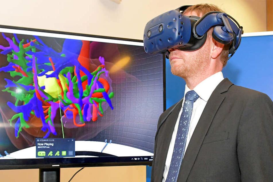 Ministerpräsident Michael Kretschmer (44, CDU) trägt im Nationalen Zentrum für Strahlenforschung in der Onkologie eine Virtual-Reality-Brille und betrachtet eine vom Krebs befallene Leber.