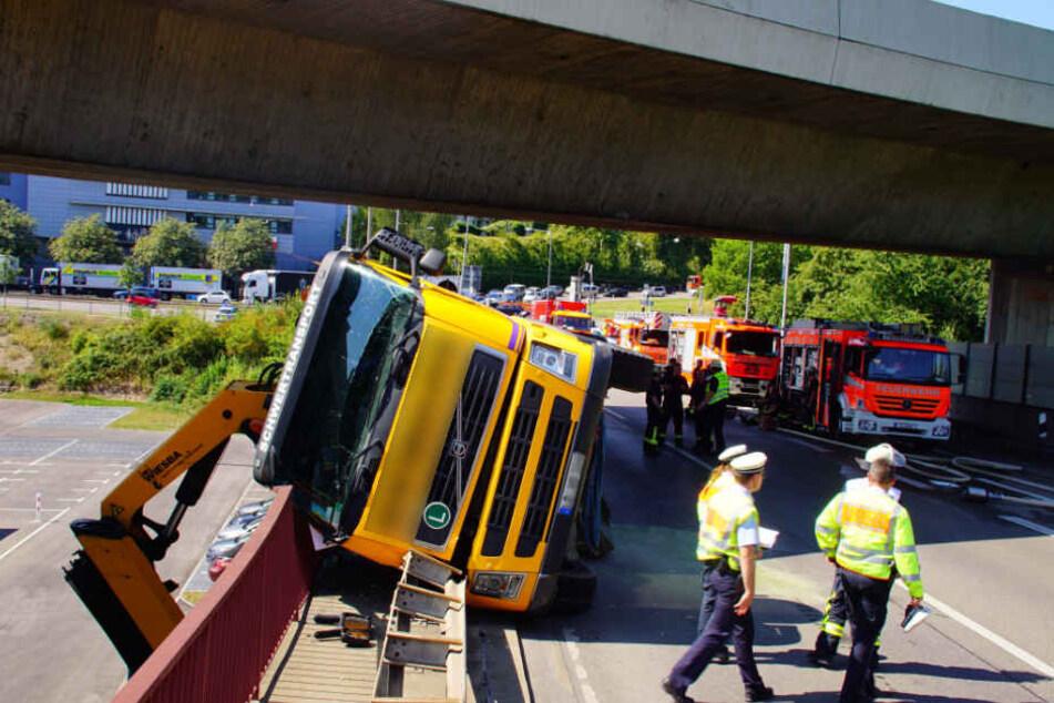 Der Unfall-Truck liegt auf der Seite, der Kran hängt über den Rand der Brücke.