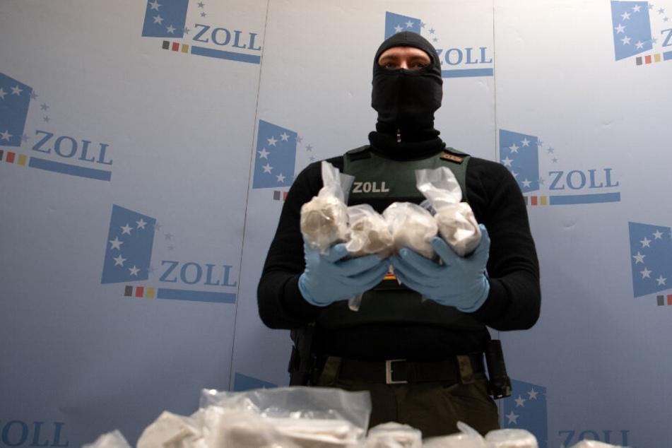 Ein vermummter Angehöriger der Zollbehörde präsentiert mehrere Pakete Rauschgift. (Symbolbild)