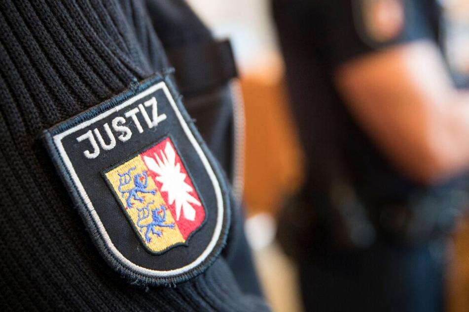 Justizbeamte stehen im Gerichtssaal.