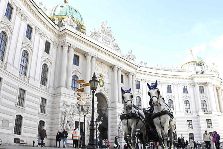 ine Pferdekutsche fährt am Michaelerplatz vor der Wiener Hofburg entlang.