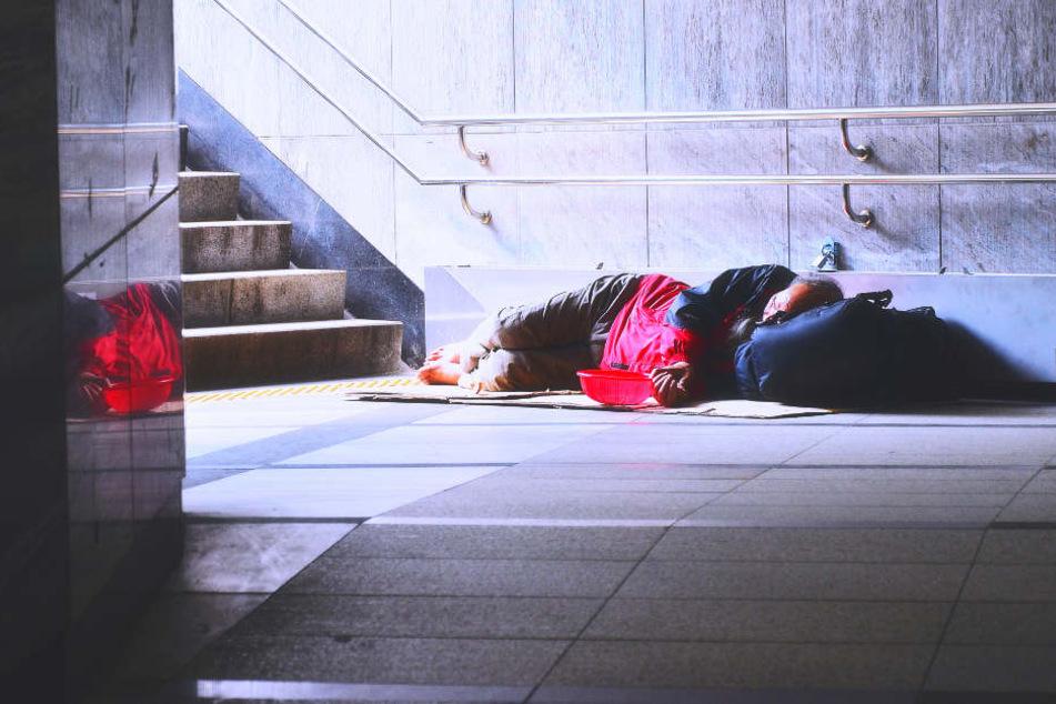 Ein Obdachloser liegt Treppenbereich eines U-Bahnhofes.