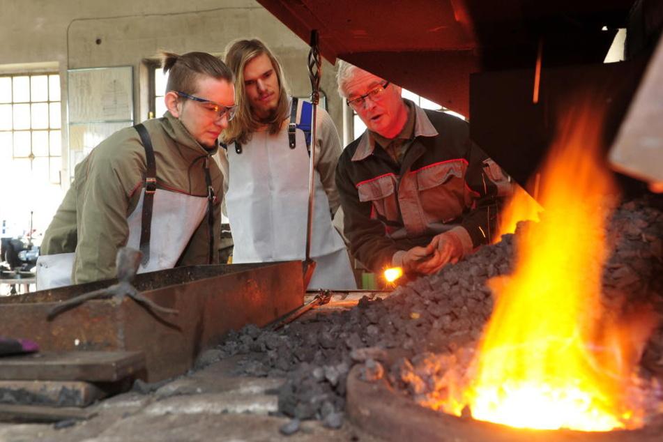 Seinen Schülern Erik Fischbach (27) und Sascha Duschek (18) er- klärt Meister Johannes Tauscher (64), wann die Eisen im Schmiedefeuer die richtige Temperatur haben.