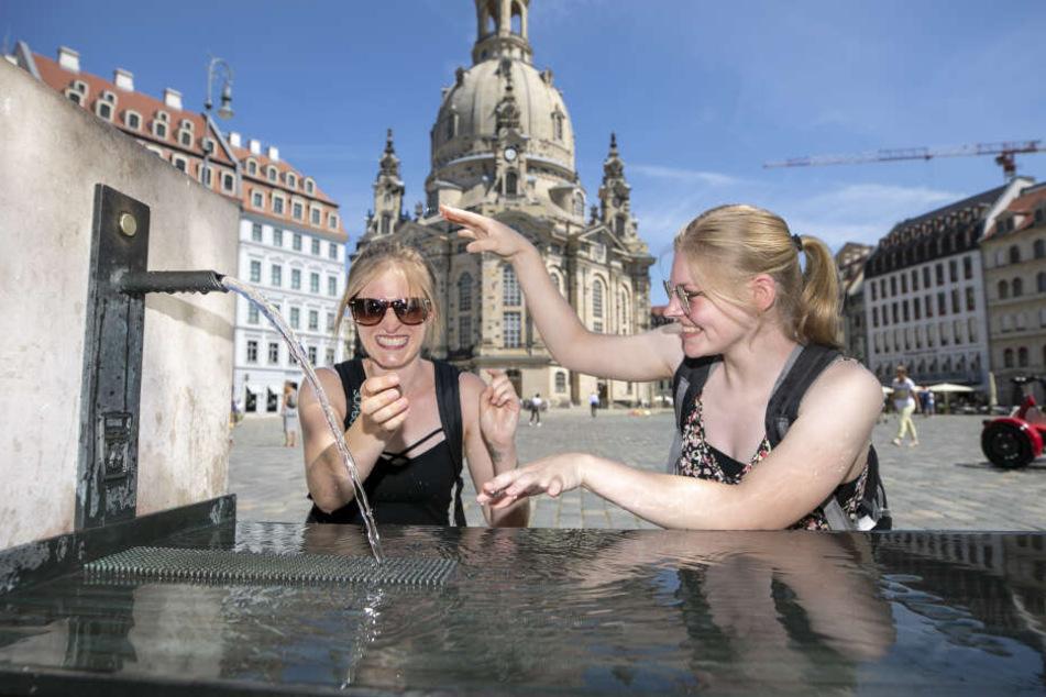 Herrlich: Auf dem schattenlosen Neumarkt kühlen sich Nadine (23, l.) und Janina (20) am Trinkbrunnen ab.