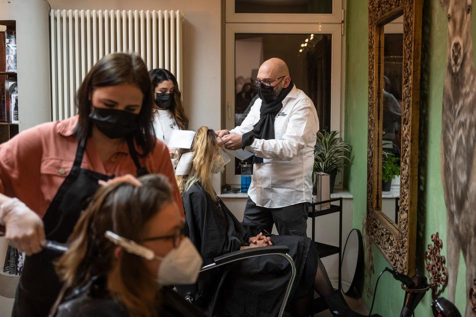 Der Dortmunder Friseur Marco Trapani und zwei seiner Angestellten schneiden kurz nach Mitternacht zwei Kundinnen die Haare.