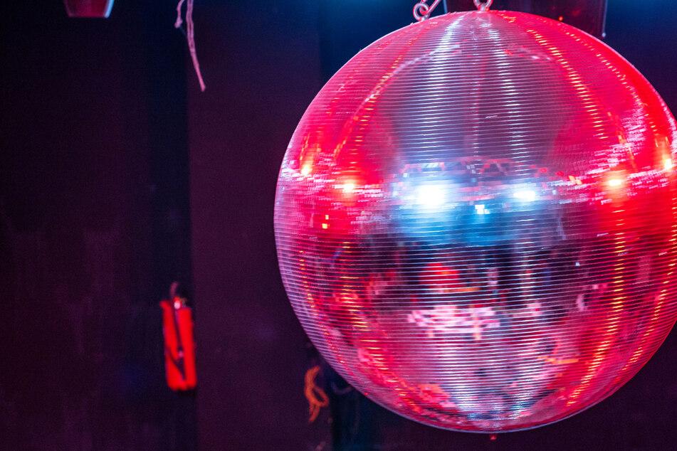 Die farbig beleuchtete Discokugel dreht sich über der Tanzfläche in einer Diskothek - viele Club-Betreiber in Hessen sehen die neuen Corona-Regeln in dem Bundesland skeptisch.
