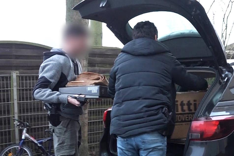 Castrop-Rauxel: Bei einer Razzia laden Zivilermittler der Polizei vor einem Haus Kartons in ein Auto.