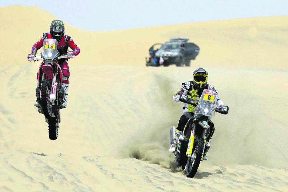 Sowohl Kräder als auch Geländewagen wühlen sich auf der Rallye durch den Wüstensand.