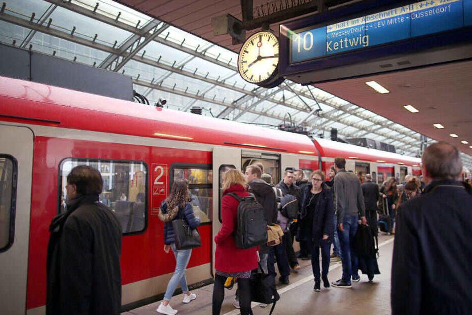 Pendler stehen an einer S-Bahn im Kölner Hauptbahnhof.